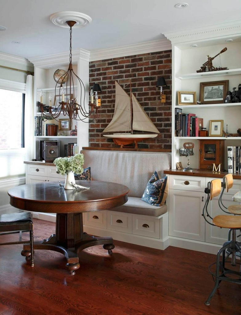 A brick wall featuring two black shaded sconces is the highlight of this nautical inspired kitchen banquette in Toronto
