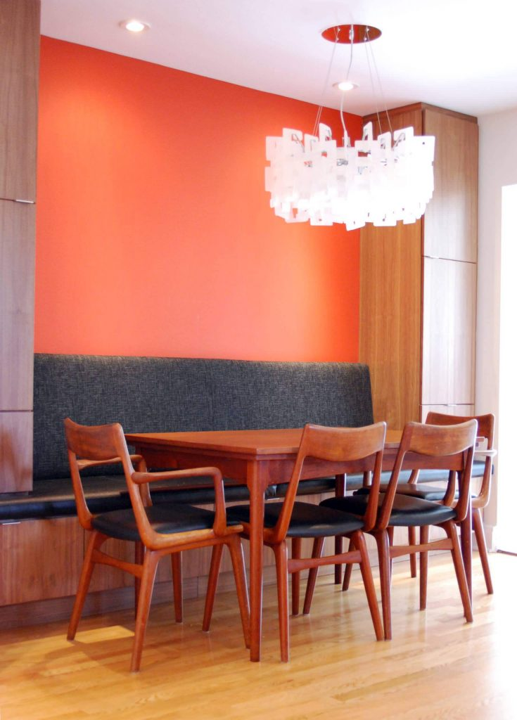 A bright orange wall pops against the charcoal gray banquette in this Ottawa, Ontario, kitchen