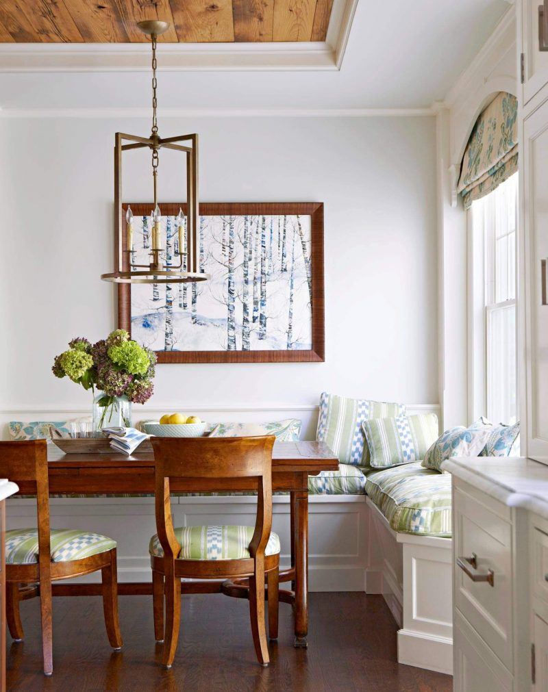 A custom banquette is paired with an antique table and chair in this Westchester, Connecticut, kitchen corner