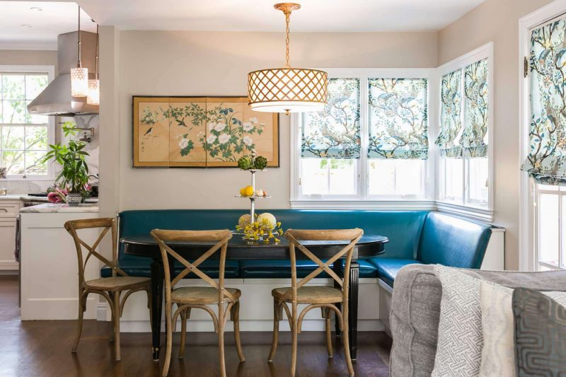 A custom peacock blue banquette, an Asian silk screen and peacock inspired Roman shades make for an elegant San Francisco kitchen nook