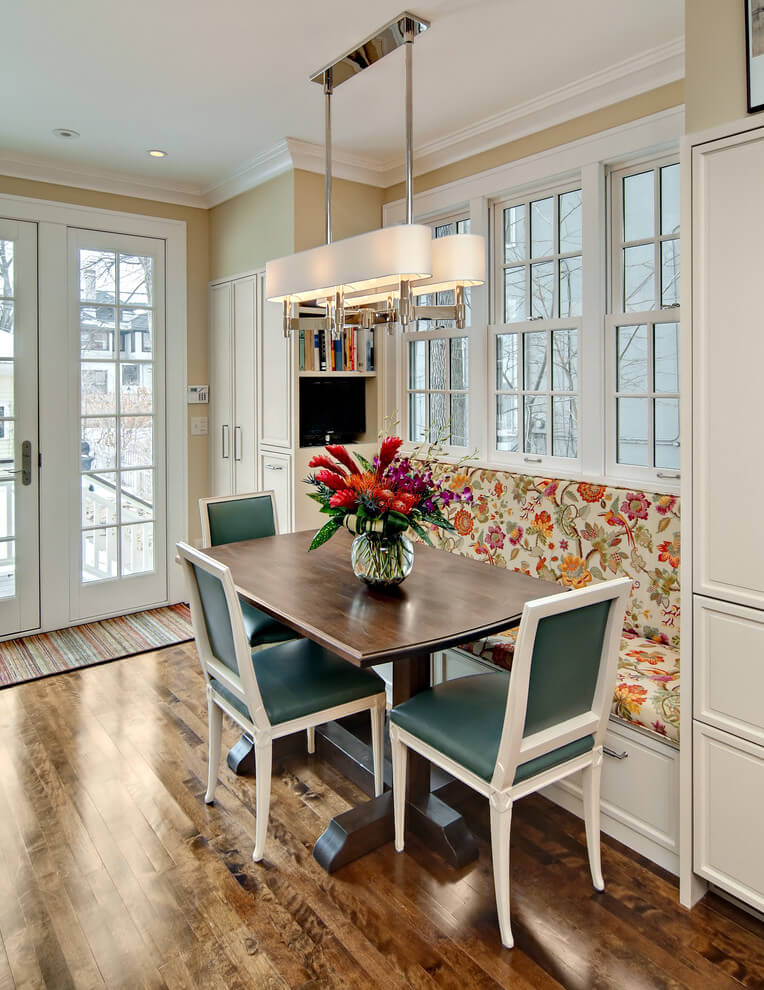A floral patterned fabric on the banquette and dark teal leather dining chairs make for a sophisticated breakfast nook in Minneapolis