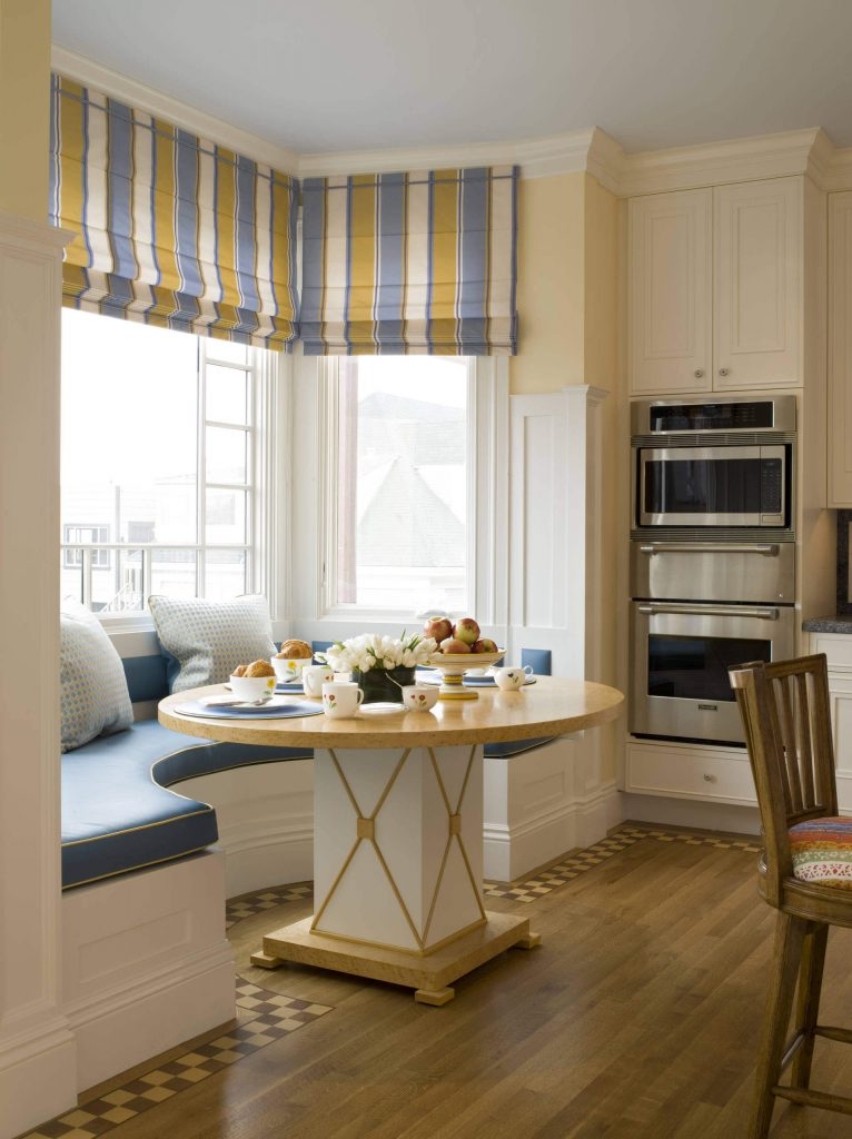 A rounded banquette covered in a light blue and gold trim is complemented by the similarly hued striped drapes found in this San Francisco kitchen