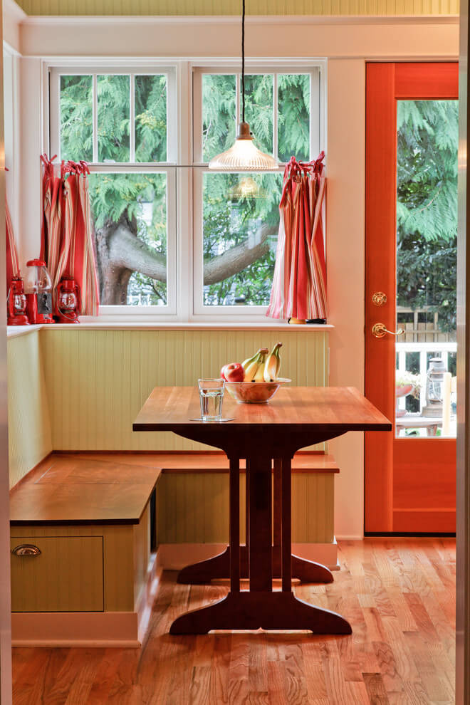 A trio of red lanterns complements the beadboard banquette painted in Benjamin Moore's Pale Sea Mist in this rustic Seattle kitchen