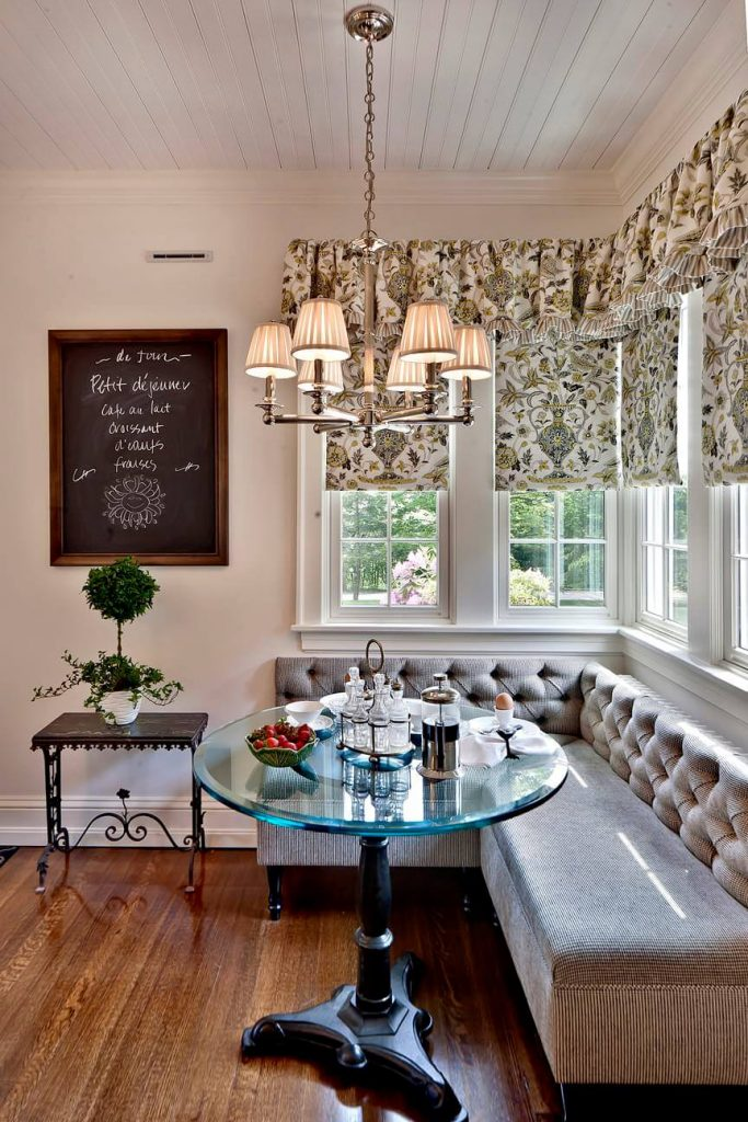 A tufted banquette and glass topped bistro table grace this traditional kitchen