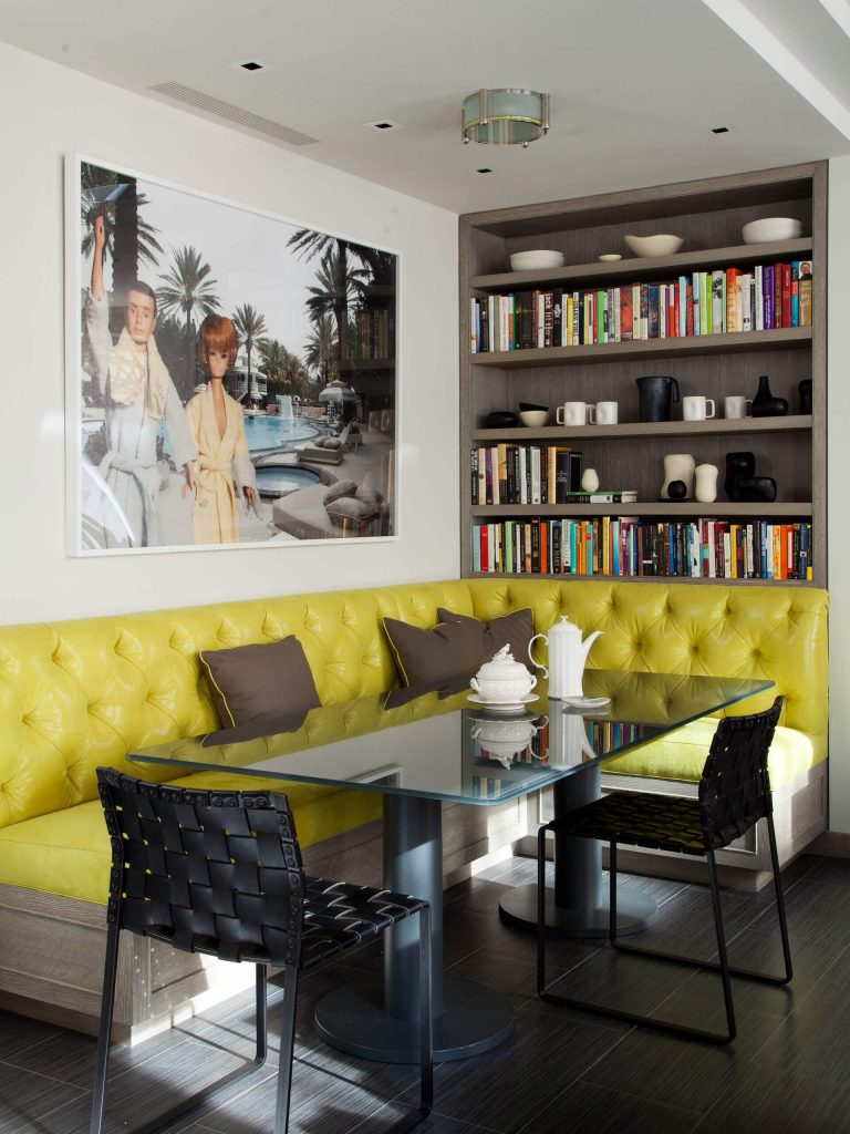 A tufted yellow leather banquette and Barbie doll inspired art make for an eclectic breakfast corner in New York