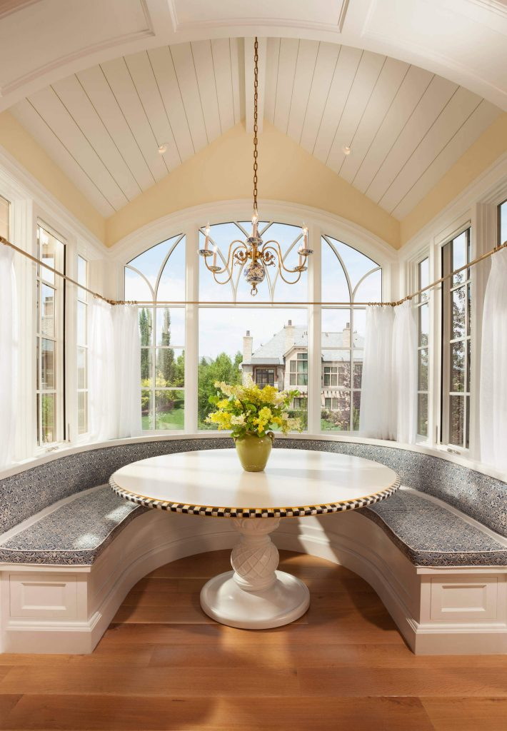 An arched ceiling designed by Think architecture Inc., with a chandelier, makes for an elegant breakfast nook in Salt Lake City