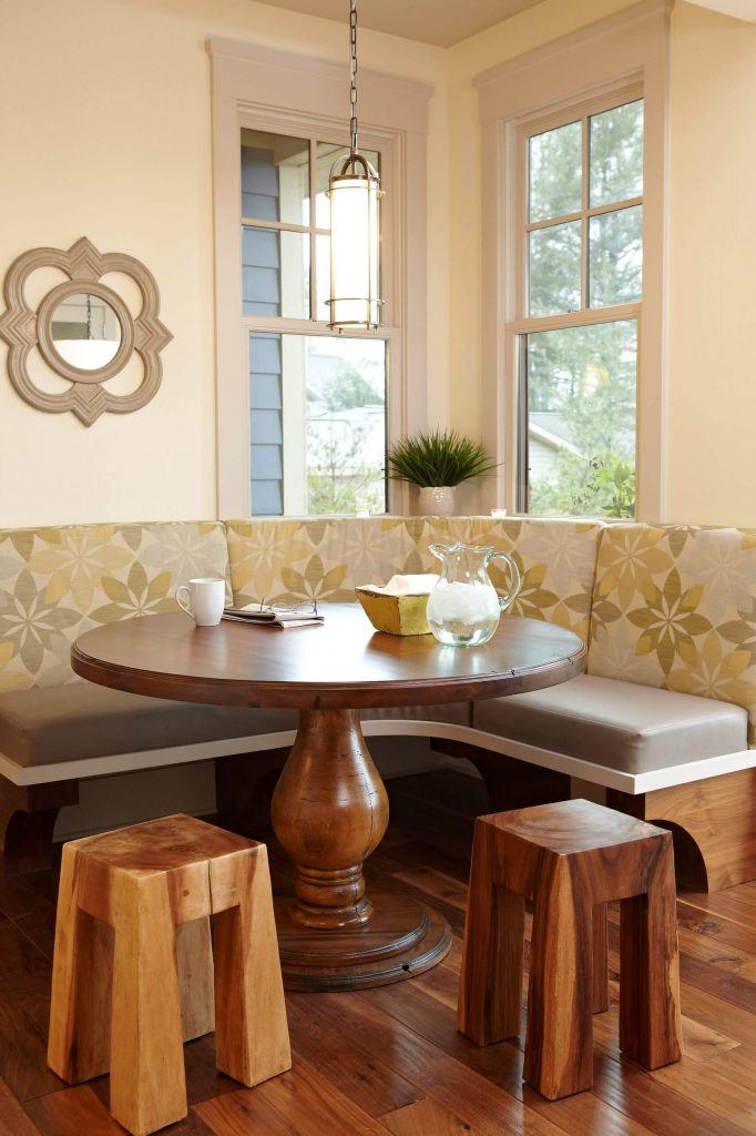 Chunky wood stools sit across from a round dining table and two toned breakfast banquette that create a stylish look for this Pentwater Lake, Michigan, kitchen