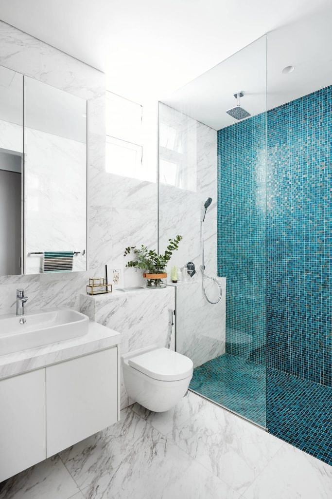 Example of a trendy blue tile, white tile and mosaic tile marble floor walk in shower design in Singapore with flat panel cabinets, white cabinets, a wall mount toilet and a vessel sink