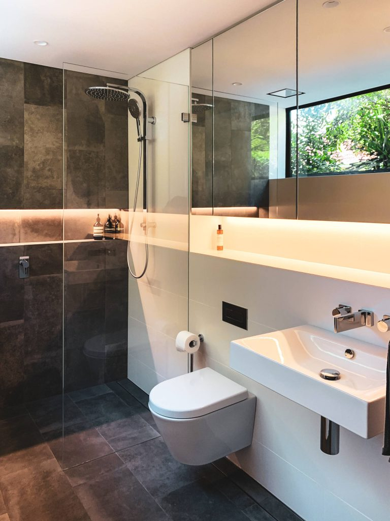 Inspiration for a contemporary gray tile and white tile gray floor bathroom remodel in Sydney with a wall mount toilet, white walls and a wall mount sink