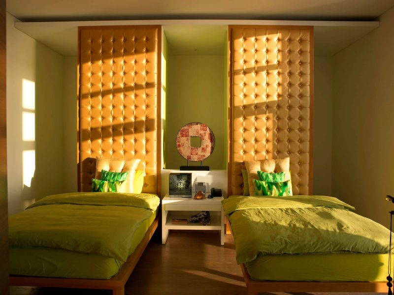 Inspiration for a contemporary guest medium tone wood floor bedroom remodel in Other with green walls and no fireplace.