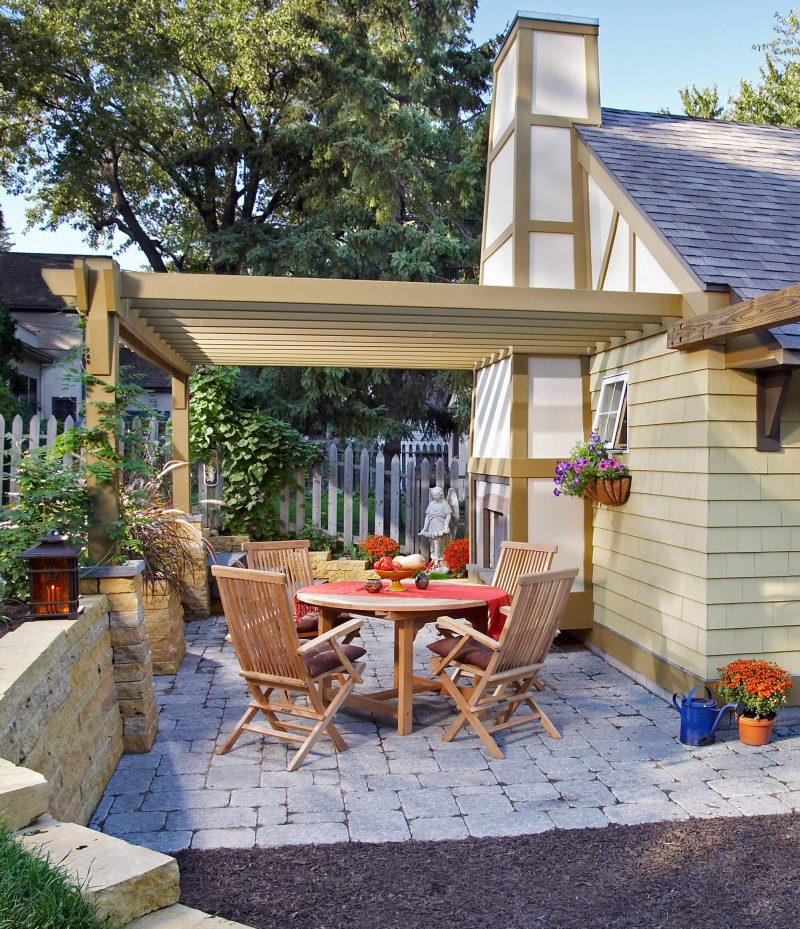 Inspiration for a small timeless backyard brick patio remodel in Minneapolis with a fire pit and a roof extension