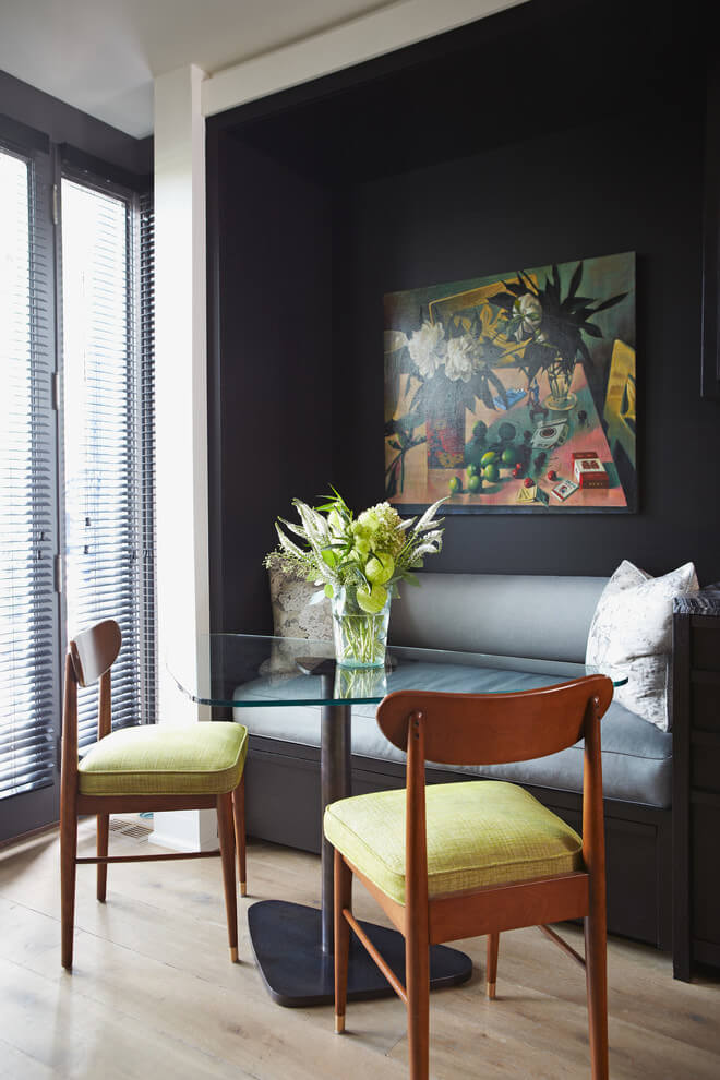 The black alcove wall provides a great contrast to the yellow cushioned dining chairs of this Toronto kitchen nook