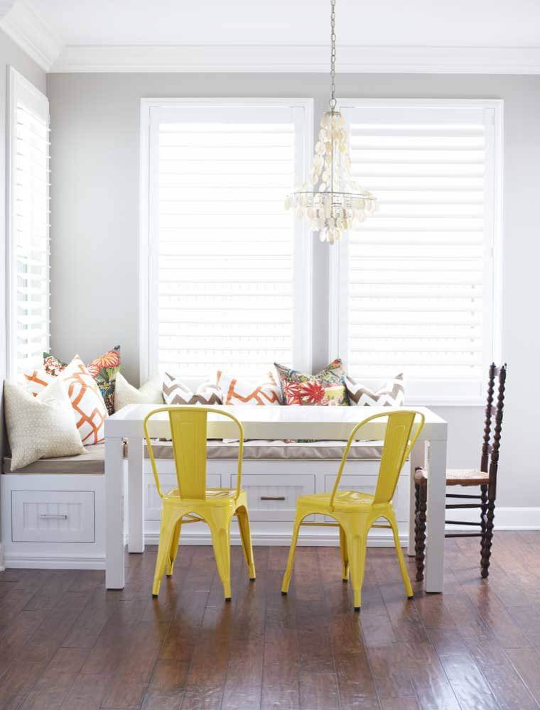 The bright yellow metal Tolix chairs make a bright splash in this otherwise neutral toned breakfast nook in San Diego