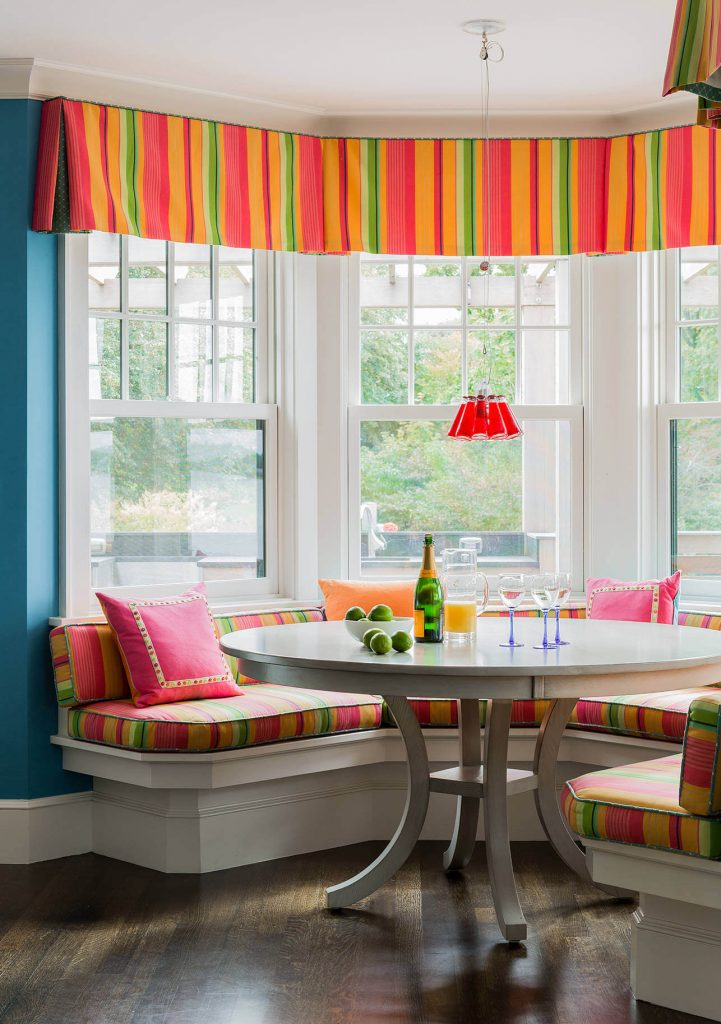 The brightly colored striped fabric that covers the banquette and valance in this Boston kitchen is paired with an Ingo Maurer Campari pendant light