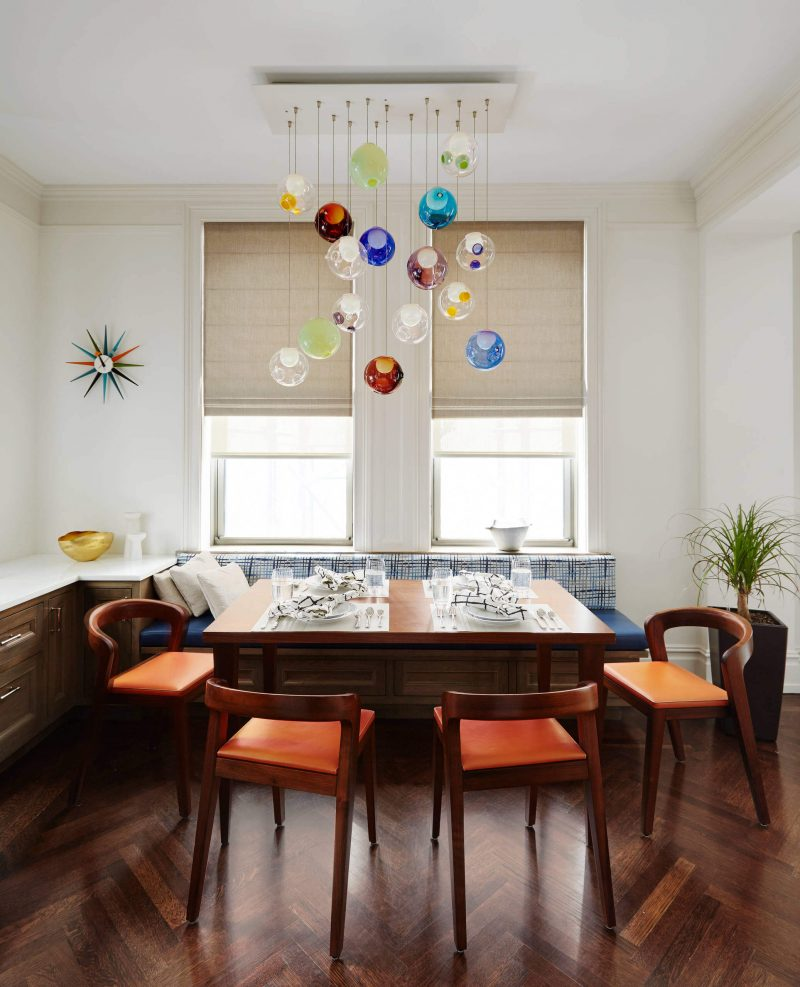 The colorful glass chandelier and Vitra Nelson Sunburst clock are highlights of this breakfast nook in Manhattan