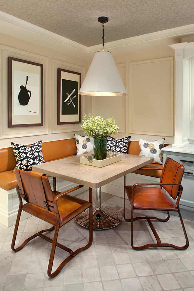 The cream paneled walls, leather covered banquette and leather strap chairs make for a handsome breakfast nook in Manhattan