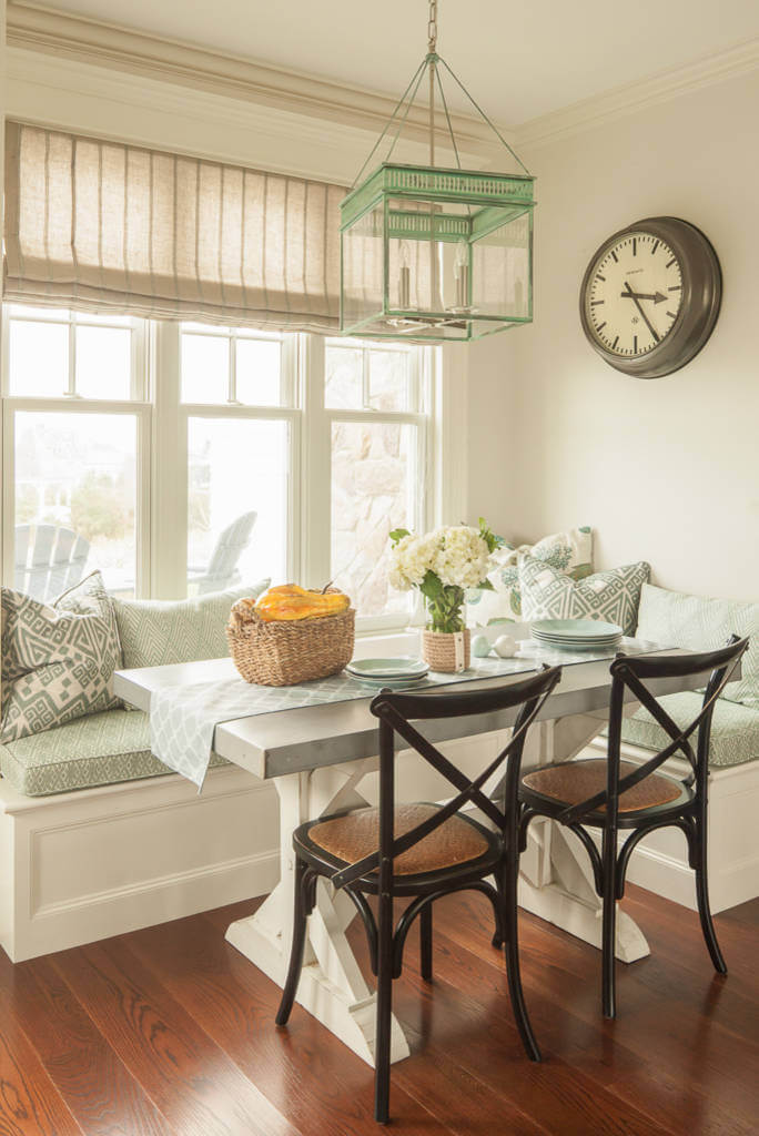 The mint green glass lantern pendant from The Urban Electric Co. blends well with the fabric covering the banquette in this Portland, Maine, beach inspired kitchen corner