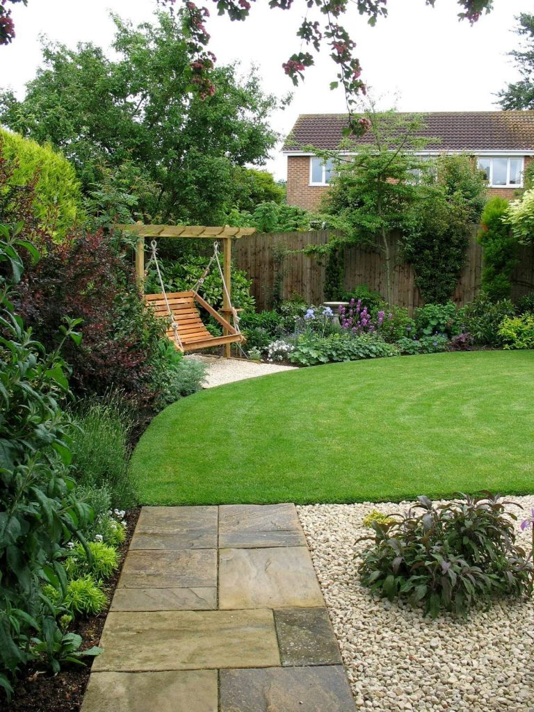 The new lawn makes the garden seem bigger and deeper. It's a shallow garden with a point to the left, now concealed by trees and the swing seat. New planting contrasts purples, greys and greens.