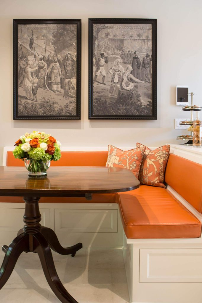 The orange faux leather covered banquette pops in this traditional kitchen breakfast area in Pasadena, California