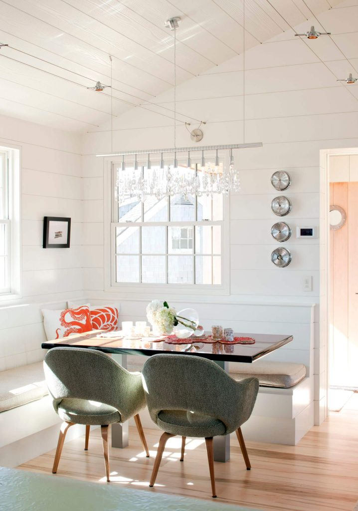 The tweed covered Saarinen armchair adds warmth and color to the all white breakfast banquette in this Philadelphia kitchen