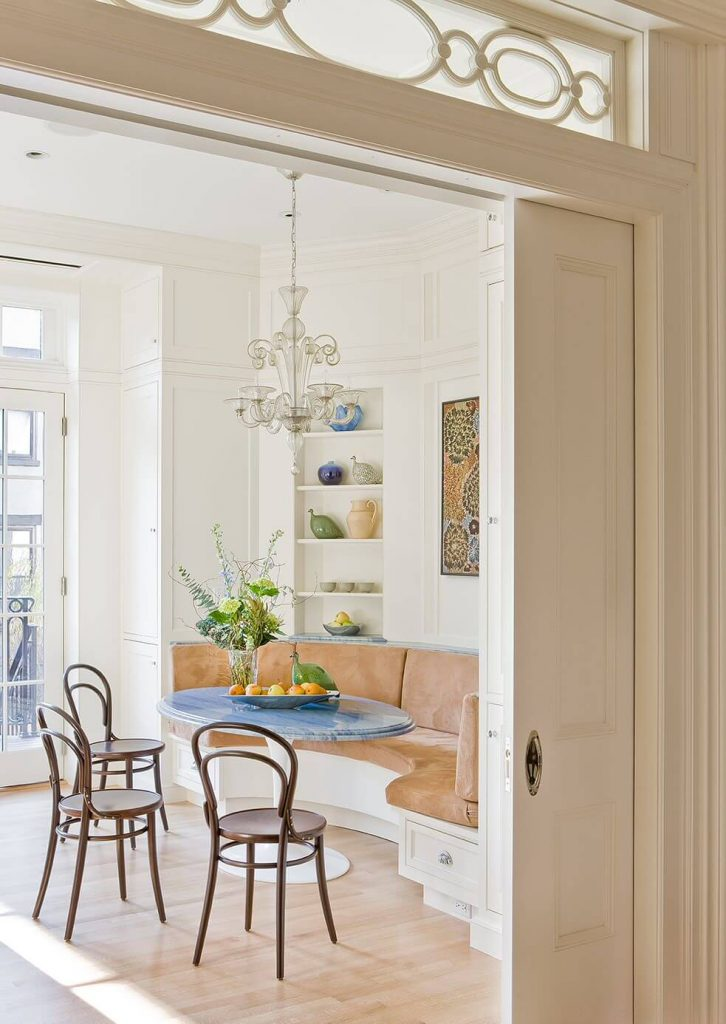 This traditional breakfast banquette in a Brooklyn Heights, New York, brownstone includes custom white cabinets constructed by Hemingway Custom Cabinetry and a smoky glass chandelier.