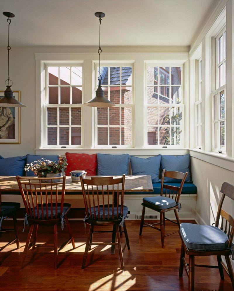 This traditional kitchen in Philadelphia has a collection of blue and red throw pillows lining the back of its built in banquette