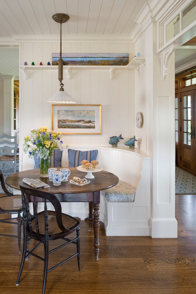 This white paneled breakfast nook in Providence, Rhode Island, features a curved banquette and an antique table.