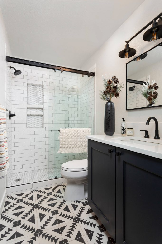 Transitional white tile and subway tile multicolored floor bathroom photo in Denver with shaker cabinets, black cabinets, white walls, an undermount sink and white countertops