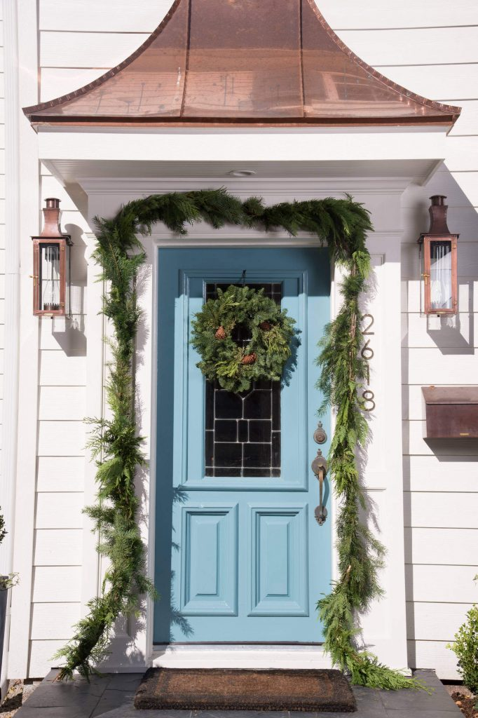 A green swag and a wreath play off this icy blue door beautifully, while copper on the lights, mailbox and pediment are warm touches.