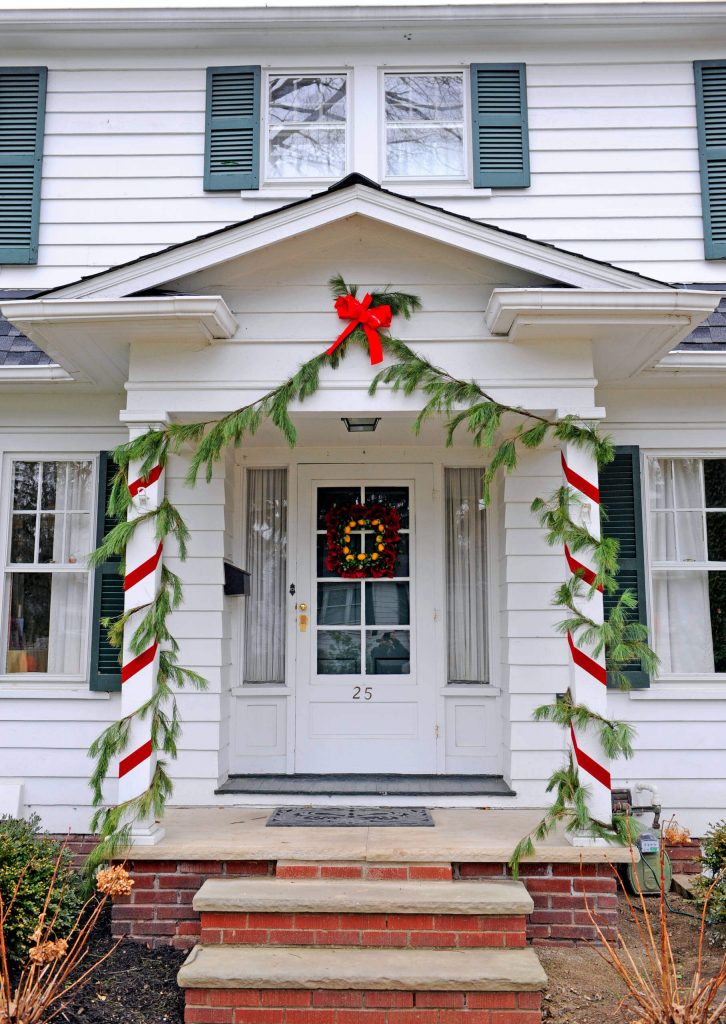 A simple combination of white pine swags and red ribbon has this traditional home all dressed up for the holidays.