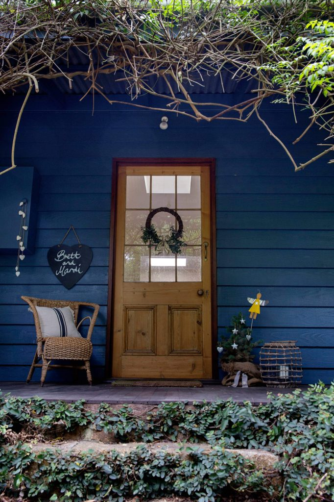 A tree topped with a sweet yellow angel spreads the holiday spirit on this front porch in Australia.
