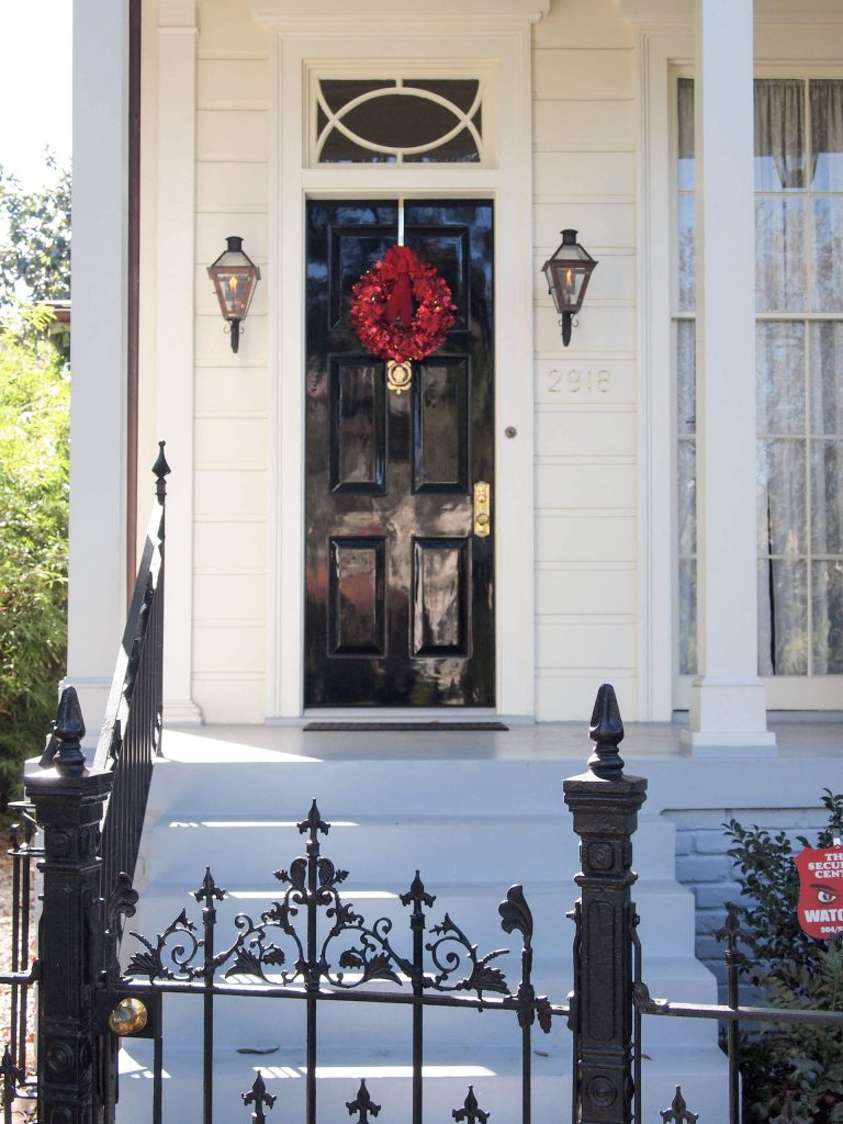 An all red wreath is a standout against a classic black and white New Orleans home.