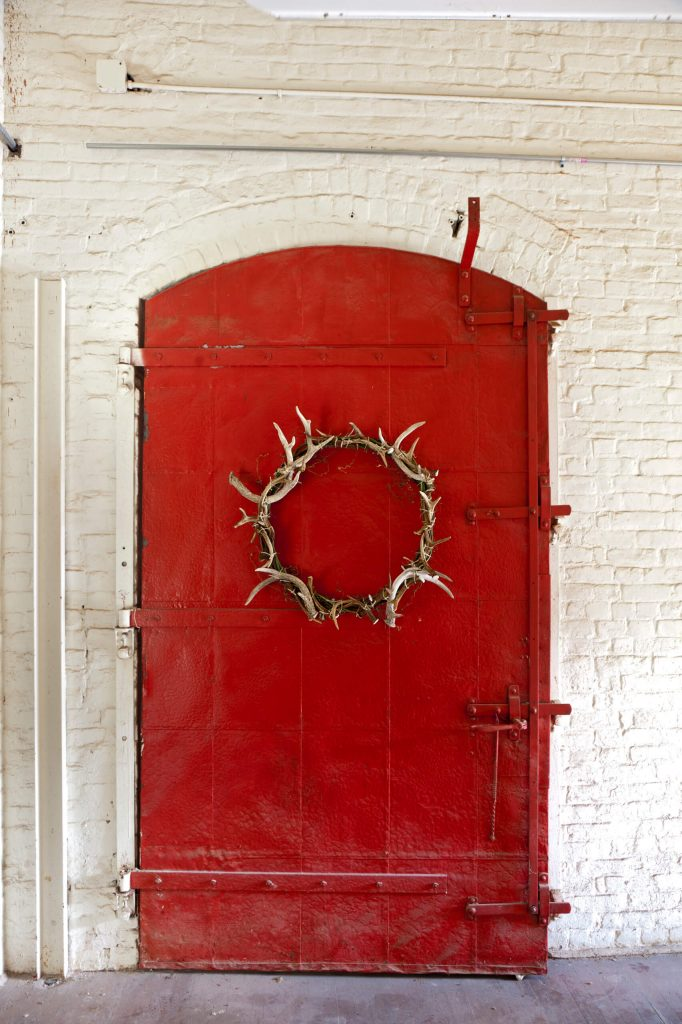An antler wreath adds just the right texture to this red industrial door.