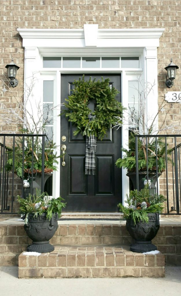"""Black, white and green create a sophisticated entry here. And note that the wreath's """"bow"""" is actually a plaid scarf."""