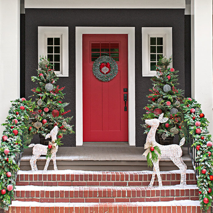 Happy reindeer and substantial garlands welcome at this front door, which is painted the perfect shade of red for the season.