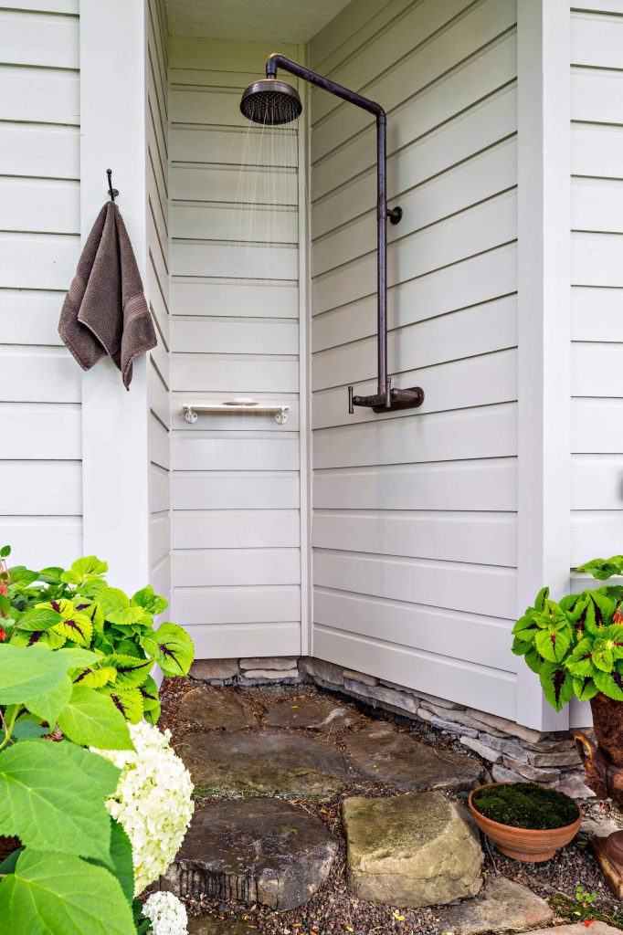 Outdoor shower is tucked into an alcove of a traditional home