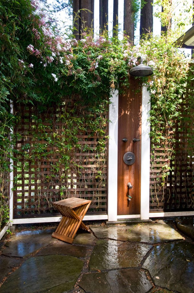 Outdoor shower set into a trellis fence in San Francisco