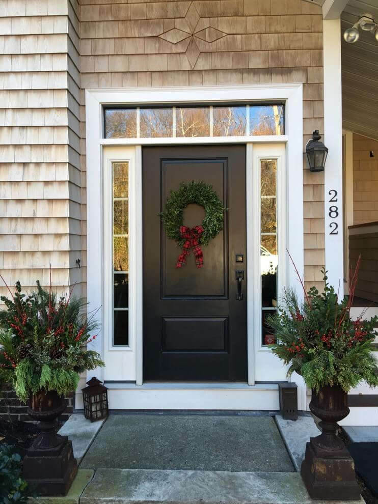 Plain boxwood with a plaid bow keep things sweet and simple, while urns festooned with branches, greens and berries amp up the entryway.