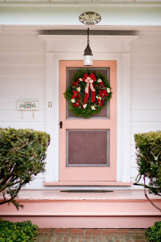 Poinsettia flowers grace the wreath on this front door.