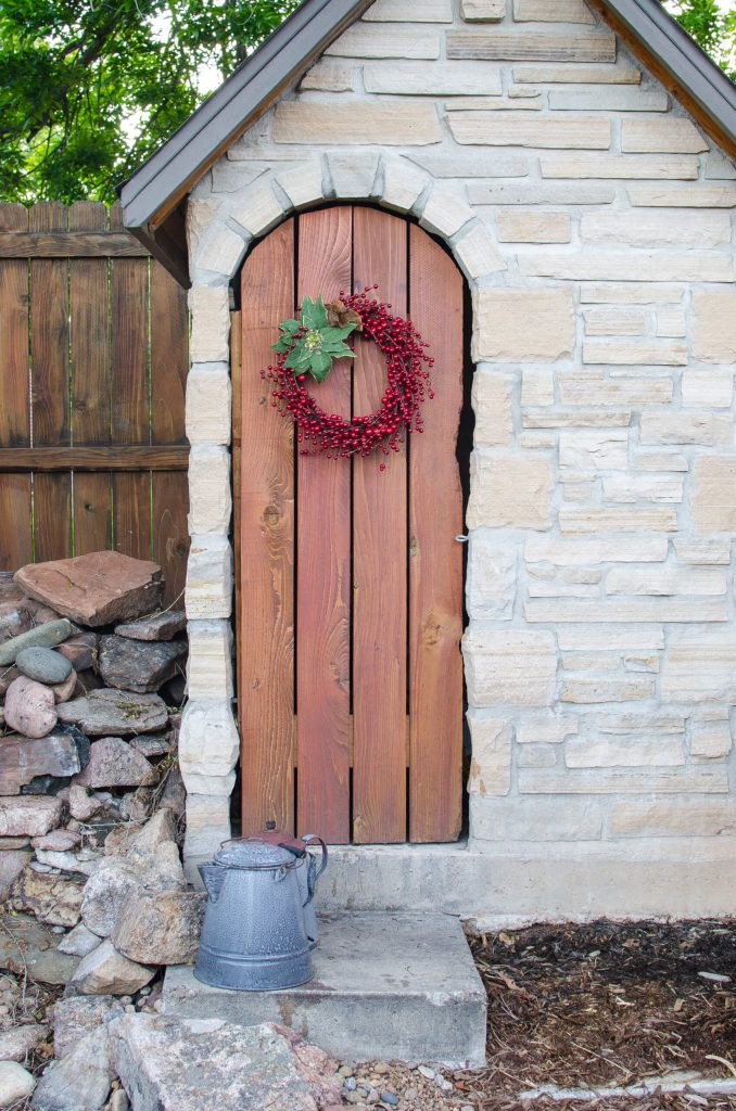 Red berries and a poinsettia flourish mark this potting shed's simple plank door.