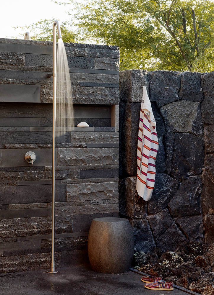 Shower wall complements the volcanic rock wall surrounding the Hawaiian property
