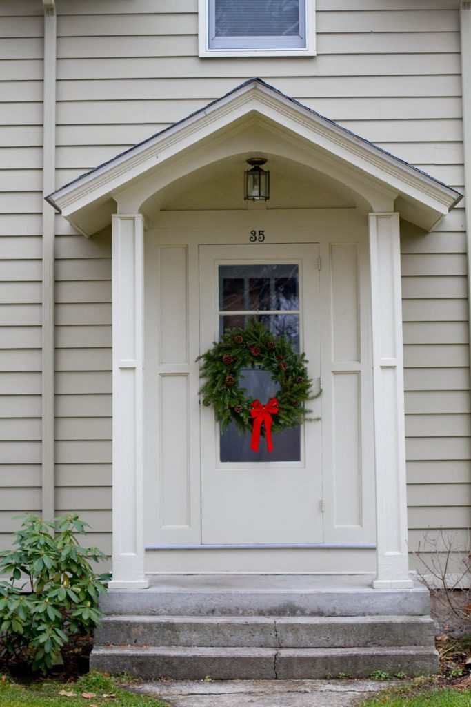 The center of the door is an unusual and pleasing placement for this wreath of classic fir and pine cones with a red bow.