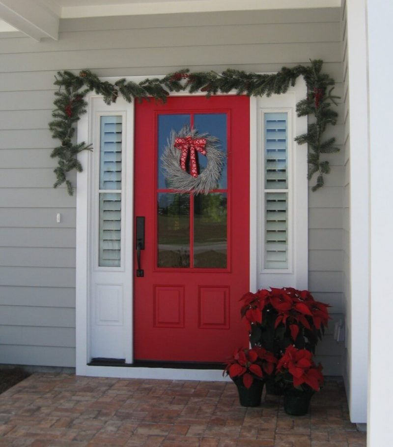 When your door is already cherry red, a wreath of twigs and a ribbon is a lovely choice. Poinsettias and a swag finish off the look.