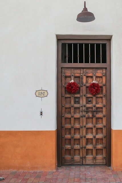 Wreaths made of red chilis feel right at home on these Tuscan doors.